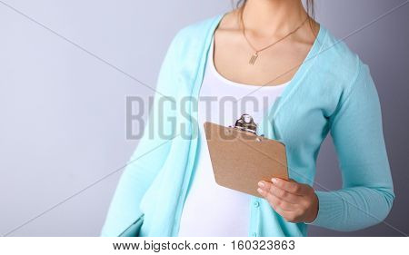 Woman with folder for documents on gray  background .