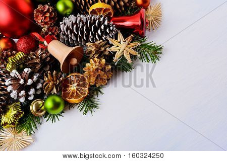 Christmas greeting card with fir branches and wooden jingle bell. Christmas decoration with baubles handmade straw ornaments and dried orange slices. Copy space.