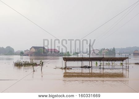 Flooded Road Junction With House In Floodwater On Rainy Day