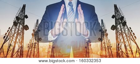 Businessman with panoramic double exposure telecommunication towers, and city in sunset background