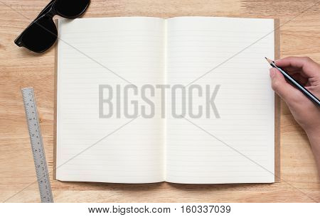 Top view of open notebook with two blank pages hand hold pencil sun glasses and ruler on wooden table