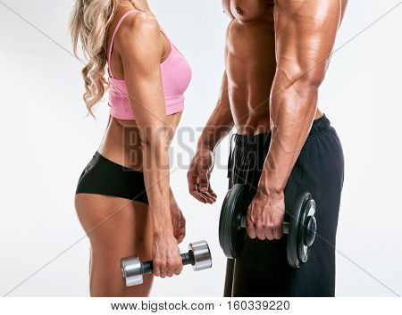 Couple man and woman muscled. bodybuilders body part on grey background