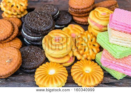 Colorful candy cookies cream on a wooden table.