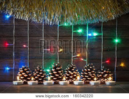 Festive new year and Christmas concept. Colorful lights of garlands fir cones and candles on the background of old barn boards