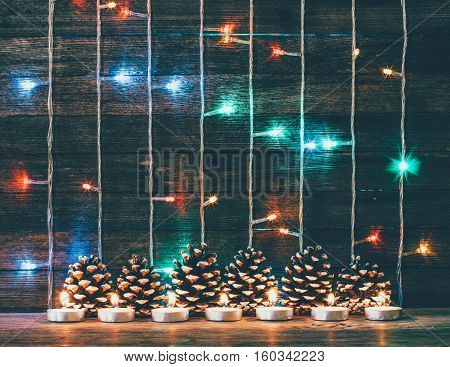 Festive Christmas New Year concept. Multicolored lights garland fir cones and candles on the background of old barn boards. Toning photo