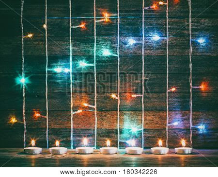 Festive Christmas New Year concept. Multicolored lights garlands and candles on the background of old barn boards. Toning photo