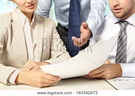 Chief manager explaining something to his two subordinates