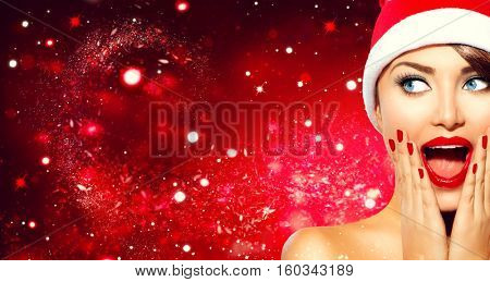 Christmas woman. Beauty model girl in Santa Claus hat with red lips and manicure looking right with a surprised expression. Closeup portrait over red holiday snow wide background copy space. Emotions.