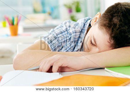 Little boy fell asleep on desk in classroom