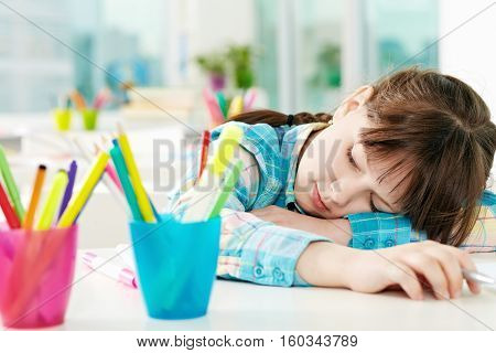 Little girl fell asleep on desk in classroom