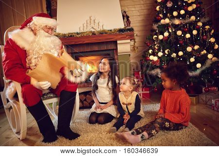 Santa Claus read children's whishes for Christmas gift from long paper