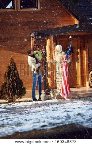 Afro American parents and child decorate house together outdoor for Christmas
