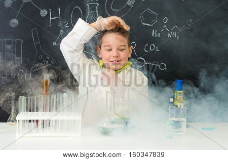 pop-eyed funny boy after chemical experiment in chemistry lab with fume