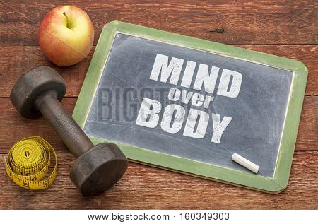 mind over body  concept -  slate blackboard sign against weathered red painted barn wood with a dumbbell, apple and tape measure