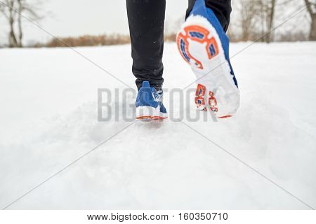 fitness, sport, people, footwear and healthy lifestyle concept - close up of male feet running along winter road and snow