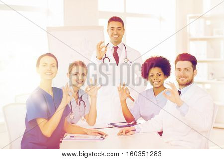 hospital, profession, medical education, people and medicine concept - group of happy doctors meeting on presentation or conference at hospital and showing ok hand sign