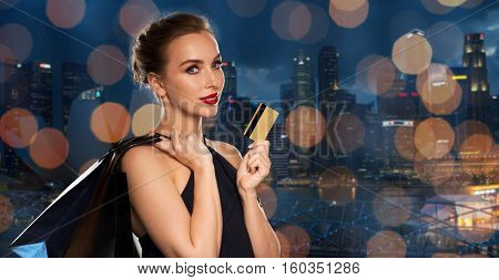 people, luxury and sale concept - beautiful woman with credit card and shopping bags over night singapore city skyscrapers and lights background