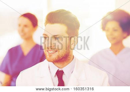 clinic, profession, people and medicine concept - happy male doctor over group of medics meeting at hospital
