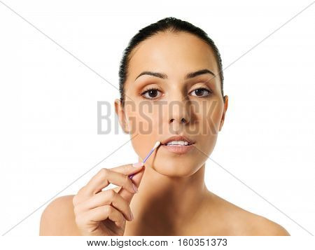 Young woman putting ear stick into mouth