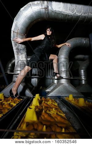 Brunette model is posing on a production line in a dark old factory leans and touching to a huge steel pipe