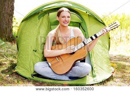 Teenage girl playing on guitar near the tent