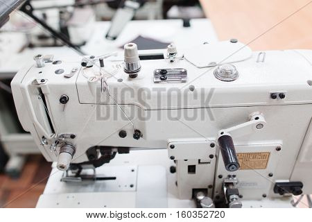 Coverstitch sewing machine close-up. Fashion designer equipment in tailor workshop. Industrial, occupation, clothes making concept