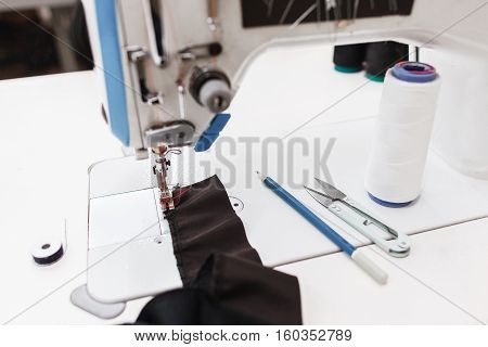 Stitching part of clothes on equipment. Close-up of dark fabric on sewing machine platform. Seamstress workplace at work time. Trying new seam, material testing, garment industry concept