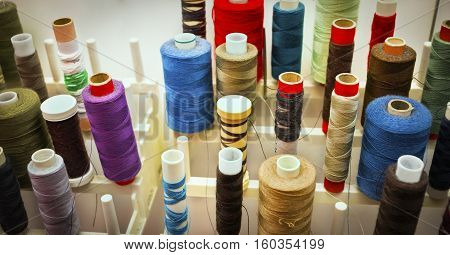 Color spools close up on a rack filled with various size thread for sewing machine