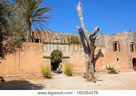 View of the bullet tree with the entrance to the refectory courtyard to the rear at Arkadi Monastery Arkadi Crete Greece Europe.