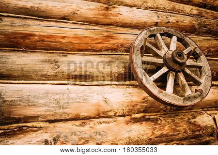 Old wooden wheel a hanging on the wall