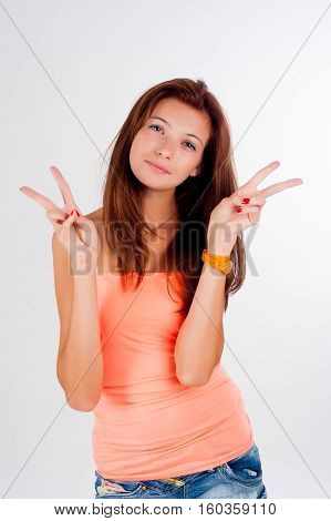 Young beautiful woman with freckles showing victory gesture and looking sideward over white background