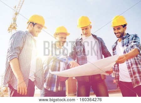 business, building, teamwork and people concept - group of smiling builders in hardhats with blueprint outdoors