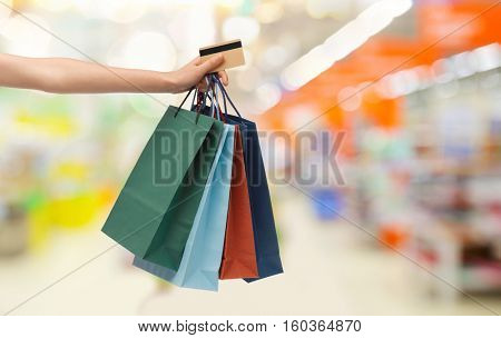 people, consumerism, finances and sale concept - hand with shopping bags and credit card over supermarket background