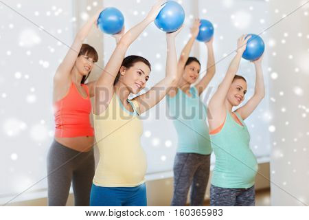 pregnancy, sport, fitness, people and healthy lifestyle concept - group of happy pregnant women exercising with ball in gym over snow
