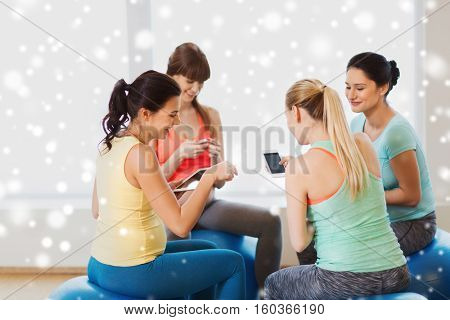 pregnancy, sport, fitness, people and healthy lifestyle concept - group of happy pregnant women with tablet pc computer and smartphone sitting on balls in gym over snow