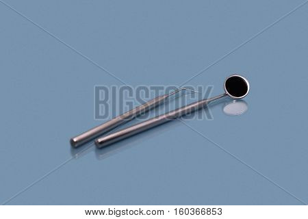 Dental mirror and dentist probe. Image isolated on blue background.