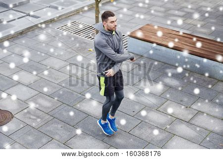 fitness, sport, people, exercising and healthy lifestyle concept - man skipping with jump rope outdoors over snow