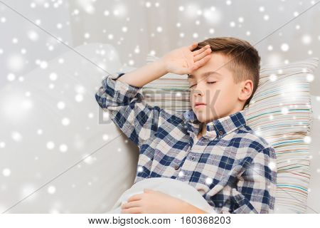 childhood, healthcare, people and medicine concept - ill boy with flu lying in bed at home and suffering from headache over snow