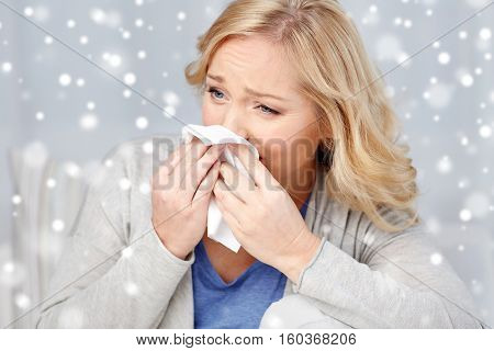 health care, flu, hygiene and people concept - ill woman blowing nose to paper napkin over snow