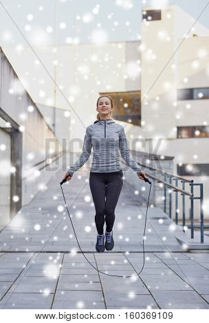 fitness, sport, people, exercising and healthy lifestyle concept - happy woman skipping with jump rope outdoors over snow