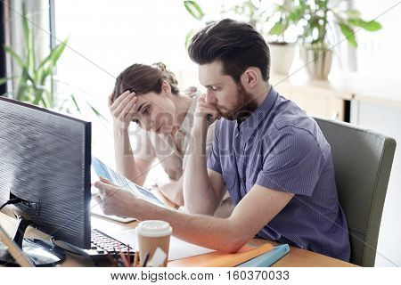 business, startup, fail, deadline and people concept - creative team with computer and files solving problem in office