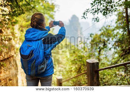 Young Female Tourist Taking Photo Of Beautiful Mountain View