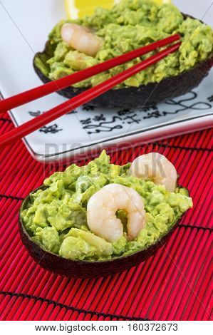 Green avocado salad with shrimps, lemon and red chopsticks lies on the white plate on the red background