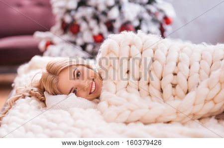 Feeling comfortable. Smiling joyful young woman lying on the bed and being covered with a warm knitted blanket while waiting for Christmas