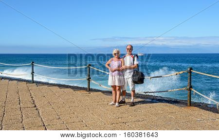 Mature tanned couple in light clothes is standing on Los Gigantes embankment on Tenerife in sunlight on bright blue water sky Gomera Island and splashing wave background.