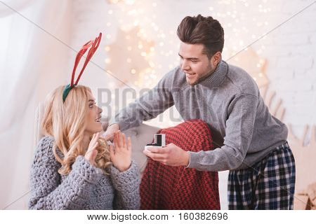 Will you be my wife. Positive nice loving man leaning forward and making a marriage proposal to his girlfriend while holding an engagement ring