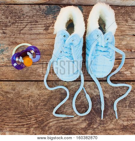 2017 new year written laces of children's shoes and pacifier on old wooden background. Toned image. Top view