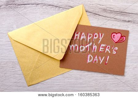 Mother's day card and envelope. Envelope on wooden backdrop. Remember to send greeting. Congratulation letter for mom.