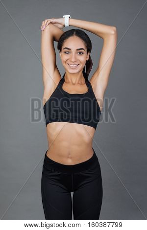 Smile and do. Happy smiling young sportswoman keeping her arms over the head bent in elbows looking straight at camera standing against grey background