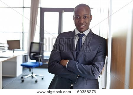 Portrait of smiling young businessman standing arms crossed leaning on cupboard in office